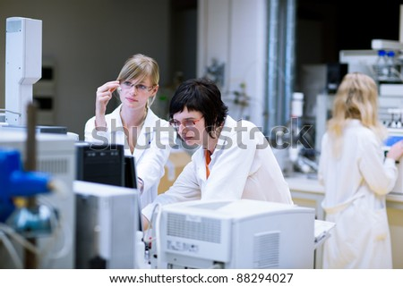 female researchers/chemistry students doing research in a chemistry lab - stock photo