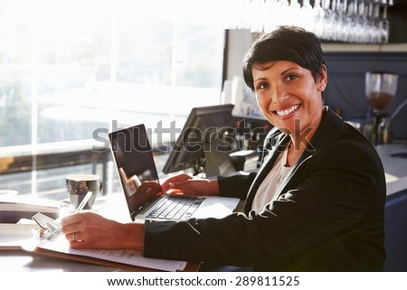 Female restaurant manager working at counter - stock photo