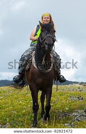 Female rider on horseback at mountains - stock photo