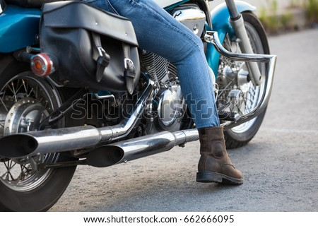Female rider ready to start traveling on the classic chopper motorcycle