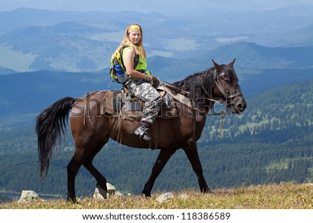 Female rider with backpack on horseback at mountains - stock photo
