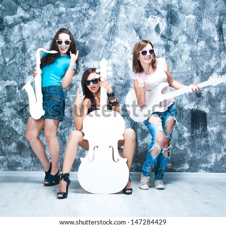 female rock band. girls with musical instruments: guitar, cello and  sax - stock photo