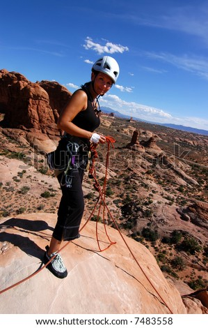 Female rock climber at the summit of desert tower - stock photo