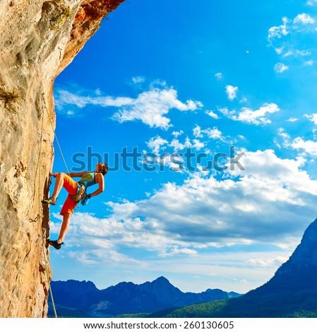 female rock climber climbs on a rocky wall - stock photo