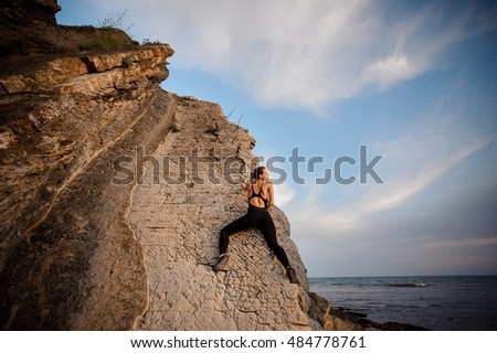 female rock climber climbs on rocky wall