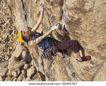 Female rock climber clings to a steep, overhanging wall.