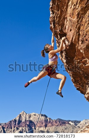 Female rock climber dangling on the edge of a steep cliff struggles for her next grip. - stock photo