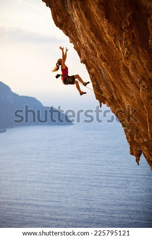 Female rock climber falling of a cliff while lead climbing  - stock photo