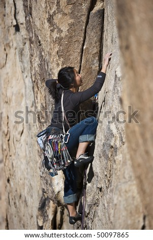 Female rock climber is focused on her next move as she battles her way up a steep cliff in Joshua Tree National Park, California.