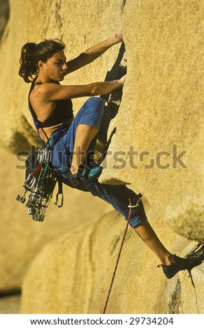 Female rock climber is focused on her next move as she battles her way up a steep cliff in the Sierra Nevada Mountains, California. - stock photo