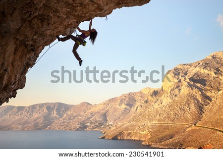 Female rock climber on overhanging cliff, Kalymnos Island, Greece  - stock photo