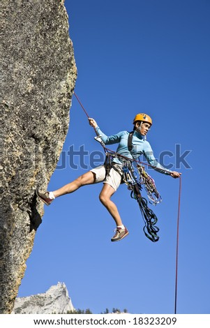 Female rock climber rappelling down a cliff in Yosemite National Park, California, on a sunny, summer afternoon. - stock photo