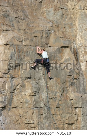 Female rock climber scaling sheer cliff face