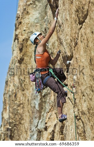 Female rock climber struggels for her next grip as she battles her way up a steep cliff in Joshua Tree National Park, California.