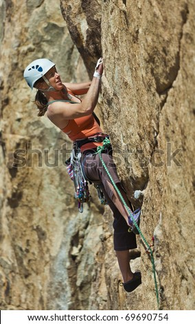 Female rock climber struggels for her next grip as she battles her way up a steep cliff in Joshua Tree National Park, California. - stock photo