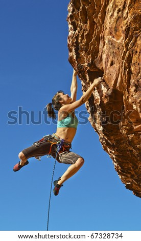 Female rock climber struggles for her next grip dangling on the edge of a steep cliff. - stock photo