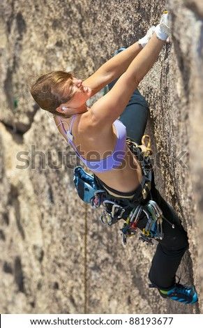 Female rock climber struggles for her next grip on a challenging ascent. - stock photo