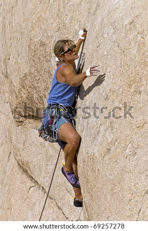 Female rock climber struggles for her next grip on the edge of a steep cliff in Joshua Tree National Park. - stock photo