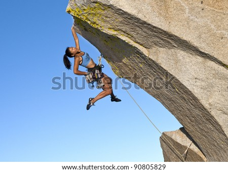 Female rock climber struggles to grip the edge of a challenging overhang.