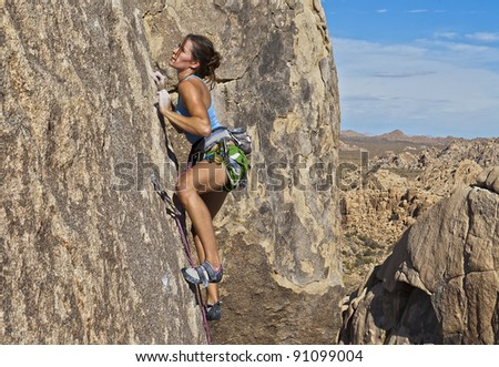 Female rock climber struggles to grip the edges on a challenging cliff. - stock photo