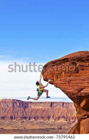 Female rock climber struggles to reach her next grip as she battles her way up a steep cliff. - stock photo