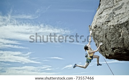 Female rock climber struggles to reach her next grip as she battles her way up a steep cliff in Joshua Tree National Park, California. - stock photo