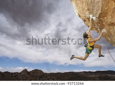 Female rock climber struggles to reach her next grip  on the edge of a challenging cliff. - stock photo