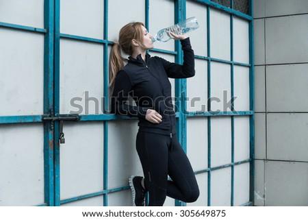 Female runner holding a bottle of water - stock photo