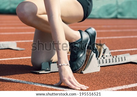Female runner in start position is ready to start the race - stock photo
