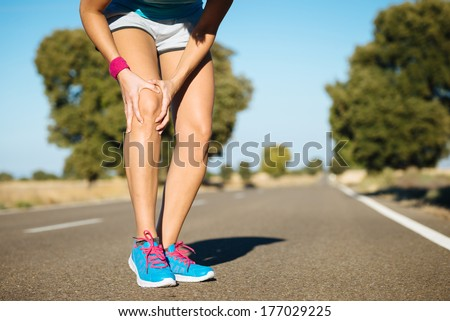 Female runner knee injury and pain. - stock photo