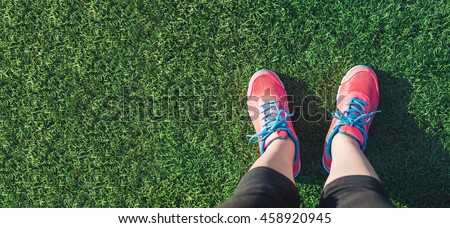 Female runner looking down at her feet in a grass field
