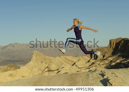 female Runner on rocky mountains - stock photo