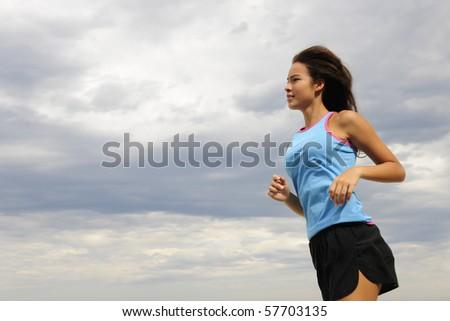 female runner on the beach running - stock photo