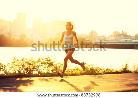 female runner running at sunset in city park. Healthy fitness woman jogging outdoors. Montreal skyline in background. - stock photo