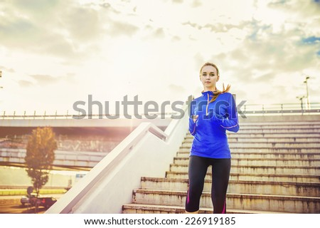 Female runner running down the stairs in city center - stock photo