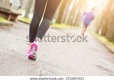 Female Runner Shoes closeup before Running at Park. Shallow depth of Field, focus on rear shoe. On background the Foothpath and some Trees. - stock photo