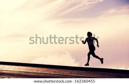 Female Runner Silhouette, Woman Running into sunset, colorful sunset sky - stock photo