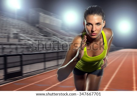 Female runner sprinter exercising and training intense track and field athlete determination for greatness in sports - stock photo