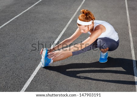 Female runner stretching before workout - outdoor shot. - stock photo
