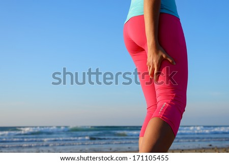 Female runner suffering from a painful hamstring muscle contracture or spasm during training. Sport leg injury during running concept. - stock photo
