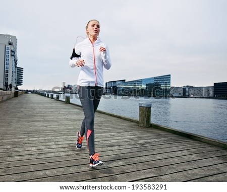 Female runner training outside. Caucasian female athlete jogging on boardwalk along river in city. Fit young woman running. - stock photo
