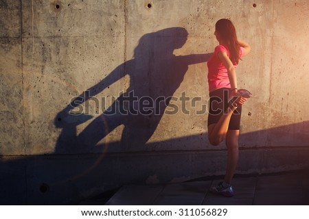 Female runner with beautiful figure doing stretching exercise before began her run, athletic woman warming up outdoors against concrete wall with copy space area for your text message or content - stock photo