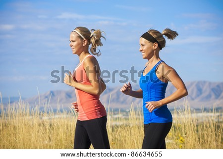 Female Runners on a jog outdoors (side view) - stock photo