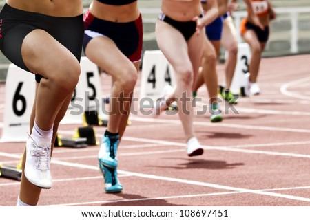 Female runners short track race start - stock photo
