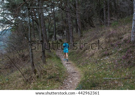 Female running in mountains at Lake Gardy, Lombardy, Italy