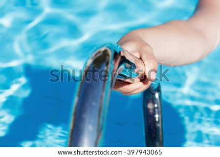 Female's hand holding a handrail in a swimming pool - stock photo