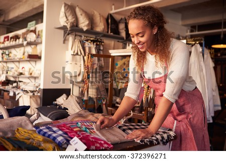 Female Sales Assistant Arranging Textiles In Homeware Store - stock photo