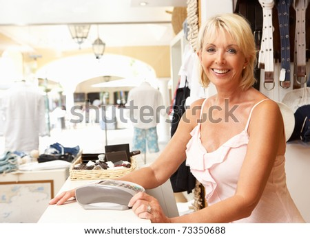 Female Sales Assistant At Checkout Of Clothing Store - stock photo