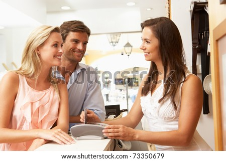 Female Sales Assistant At Checkout Of Clothing Store With Customers - stock photo