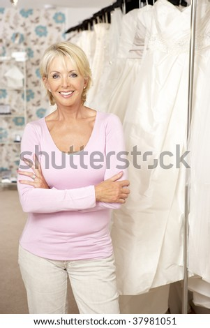 Female sales assistant in bridalwear store - stock photo